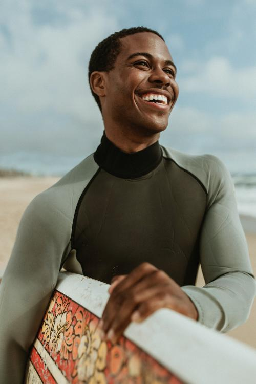 Cheerful man with a surfboard at the beach - 1079975