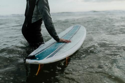 Man at the beach with his surfboard - 1080014