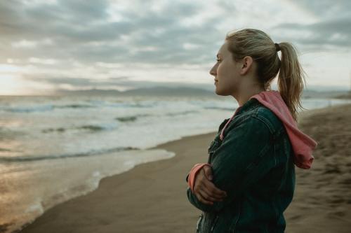 Woman on a gloomy beach - 1080053