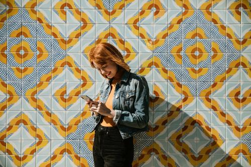 Woman using her phone at a modern patterned wall - 1198626