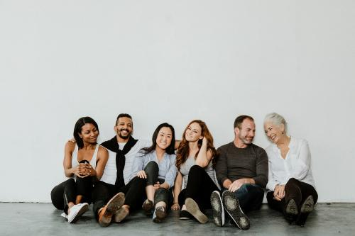 Group of cheerful diverse people sitting on a floor in a white room - 1201617