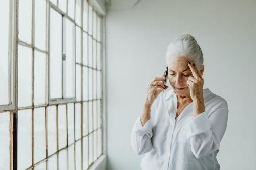Stressed senior woman talking on a phone by the window in a white room - 1201630