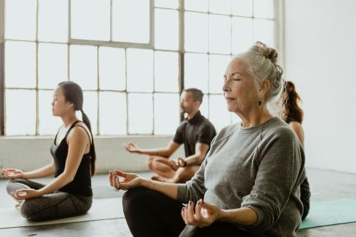 Diverse people meditating in a yoga class - 1201640