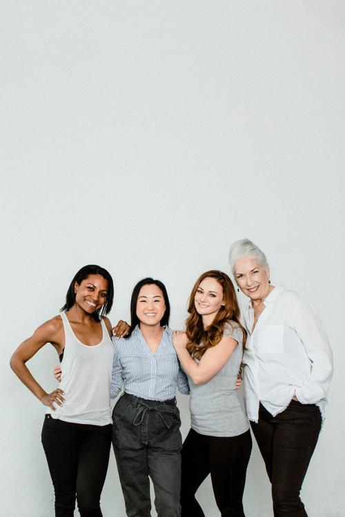 Cheerful diverse women by the window in a white room - 1201701