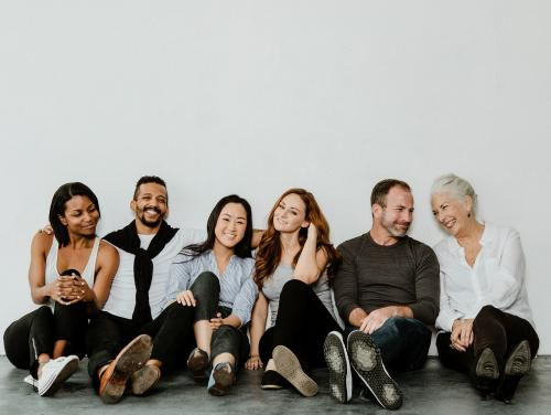 Group of cheerful diverse people sitting on a floor in a white room - 1201711