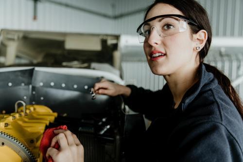 Female aviation technician repairing the motor of a propeller plane - 1202217