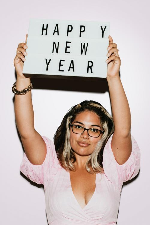 Woman with glasses raising happy new year board mockup - 1225174