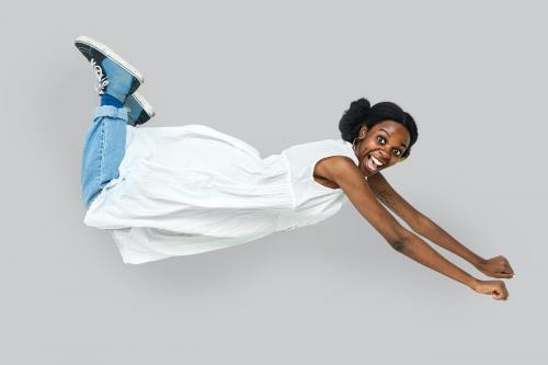 Cheerful black woman in a flying pose - 2055837