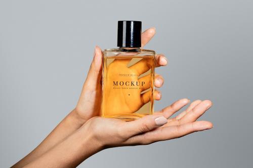 Woman holding a perfume glass bottle psd mockup - 2056048