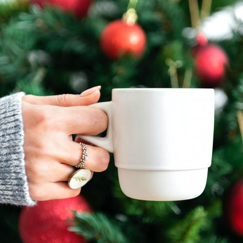 Woman holding a white cup by Christmas tree mockup - 1231827
