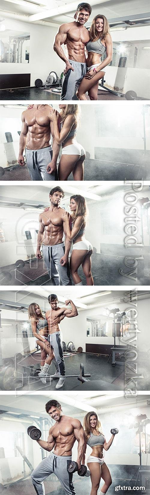 Young athletic man and girl in gym stock photo
