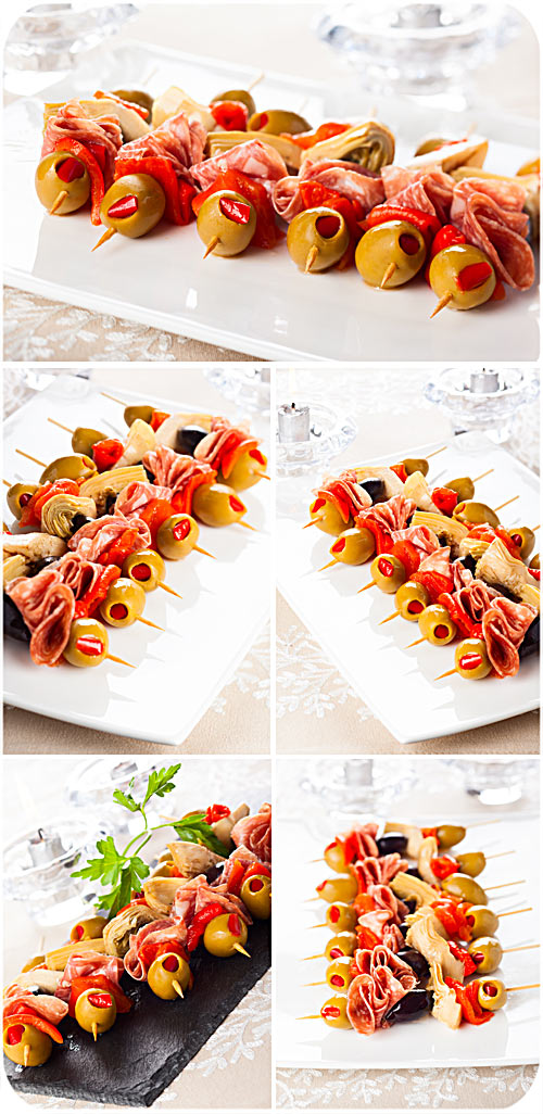 Appetizer of olives and salami on skewers - Stock photo
